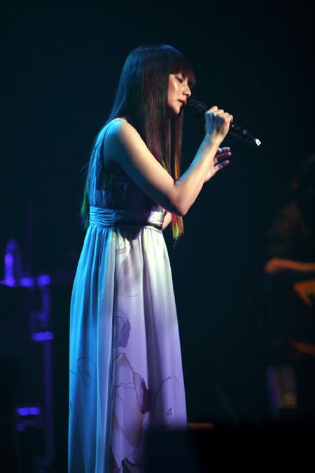 薄暗いステージで真剣な表情で歌を歌う柴咲コウ