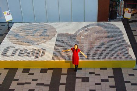 約1万個のコーヒーカップで描かれた、巨大ドットアートの前でポーズをとる菅野美穂